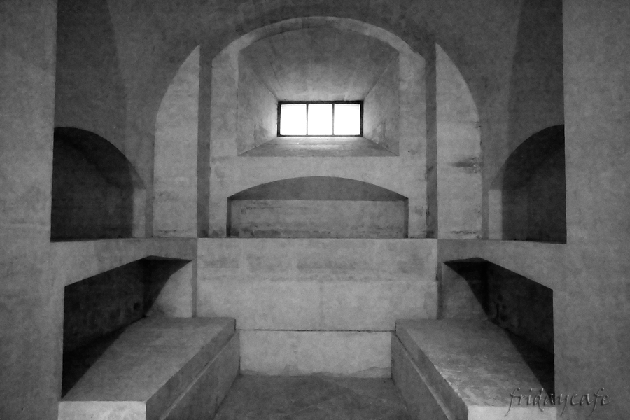 This photo shows an empty tomb in the Pantheon, with a window in the center and four empty shelves.