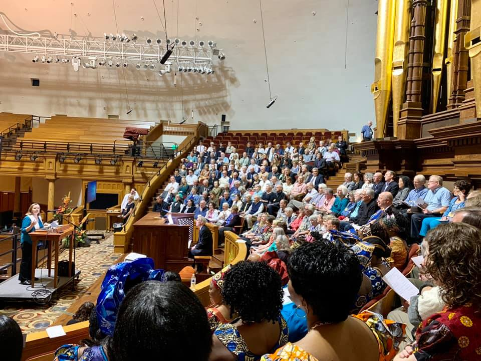 Nancy Ross is at a small pulpit on the left. In the center and on the right, a congregation sits in the choir seats at the Salt Lake City Tabernacle.