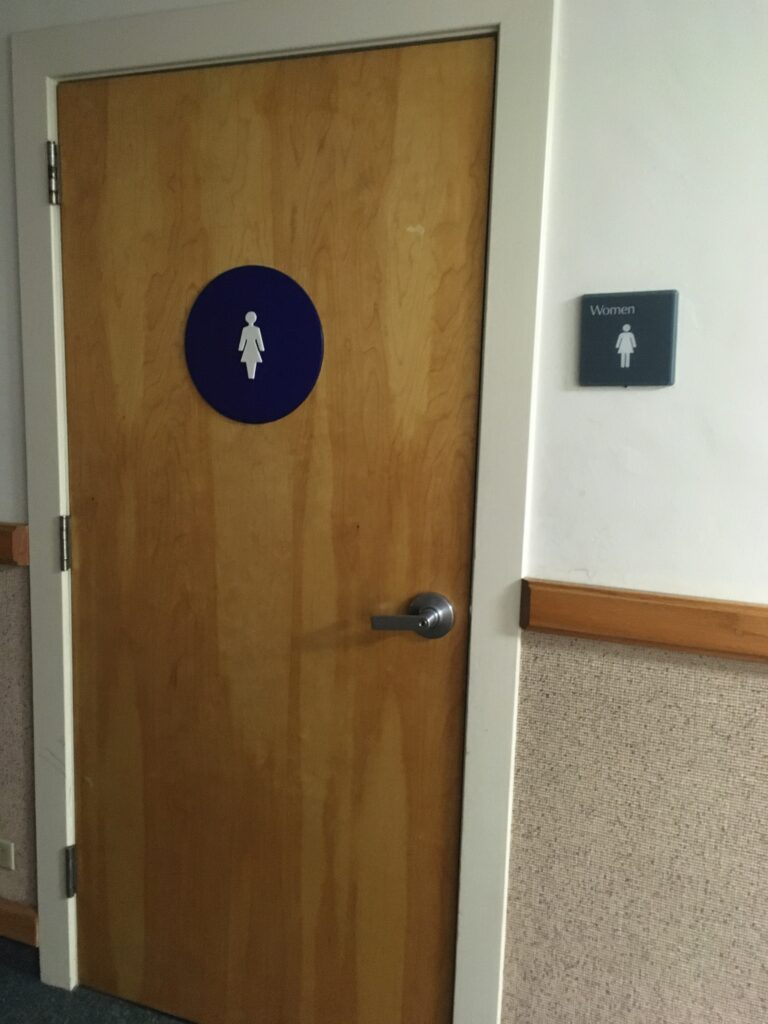 "Photo of the bathroom door and sign taken in January 2020. The door has a symbol of a woman on it and the sign says ""Women"" with the same symbol."