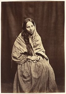 Sepia print photo of a seated woman with scarf and long dress gazes downward.