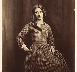 Sepia toned photo of a woman circa 1850-1858. The woman stands against a curtained background. Her long hair hangs loose, a smile on her lips. One hand rests on her hip and the other near her lap.
