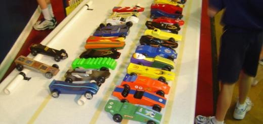 A display of pinewood derby cars at a scout meeting