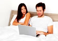 Woman upset at husband with laptop in bed. © Martinmark | Dreamstime.com