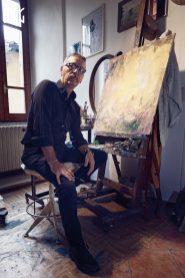 Ritratto di Giampaolo Tomassetti davanti ad una pittura nel laboratorio artistico