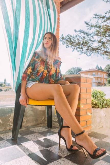 Monica Bartolucci mostra le gambe seduta in una terrazza