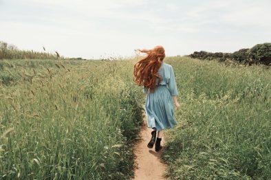 Giulia Beltrame cammina in un sentiero sterrato con i capelli rossi mossi dal vento