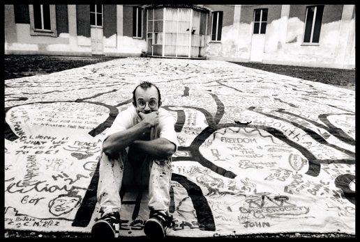 Keith Haring seduto su una sua opera fotografato da Maria Mulas