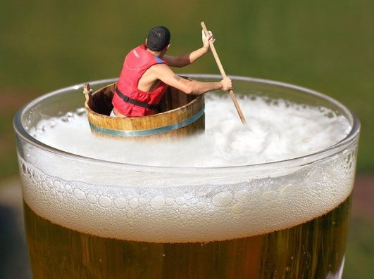 Man swimmiing in life boat on a pint of beer.