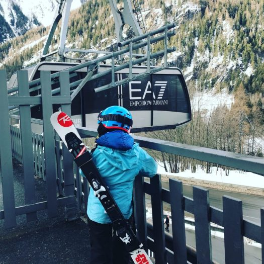 My youngest carrying his own skis with his ski strap waiting the Armani funicular to go to Plan Chécrouit in Courmayeur Mont Blanc. 7 things that can help you when taking kids skiing.