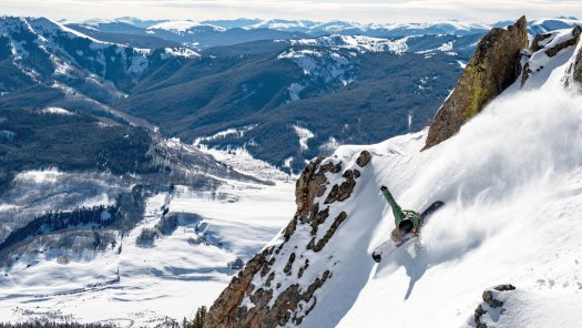 A snowboarder goes down a gully at Stevens Pass. Now part of Vail Resorts and the EPIC Pass.