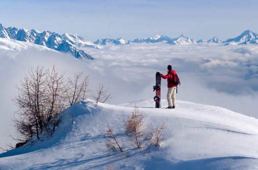 A snowboarder observes the panorama, with a cloud cover beneath him. Photo Olivier Maire- Courtesy: Crans-Montana Tourism Office.