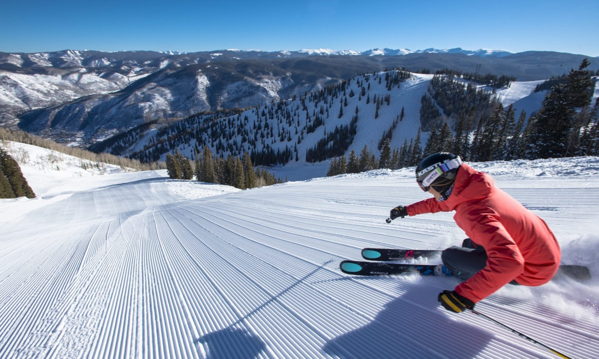 Darcy Conover skiing fresh corduroy down a steep snow covered groomed slope in the mountains at Aspen Mountain Ski Resort in Colorado - Aspen Mountain Announces Bonus Weekend June 1-2, 2019. Photo Aspen Snowmass.