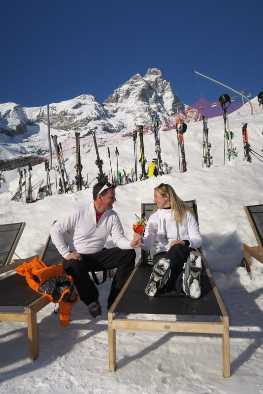 A couple taking an aperitivo by the pistes. Photo Enrico Romanzi. Breuil Cervinia Valtourneche. Breuil Cervinia. Breuil-Cervinia: chairlift failure: 27 skiers recovered by helicopter.