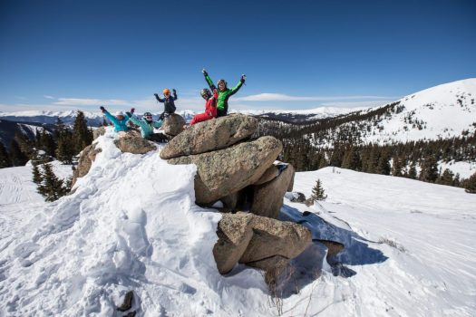 Skiers on rocks, taking a pause after a day of skiing. Photo: Dave Camara. Arapahoe Basin. Arapahoe Basin is now part of the IKON Pass.