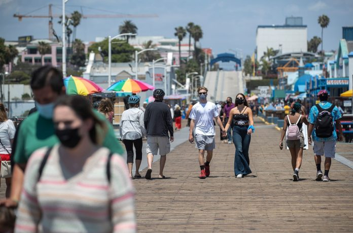 People wear face coverings as they walk the Santa Monica pier on Monday