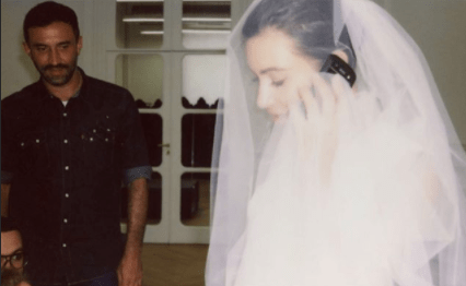 Kim on the phone in the wedding dress
