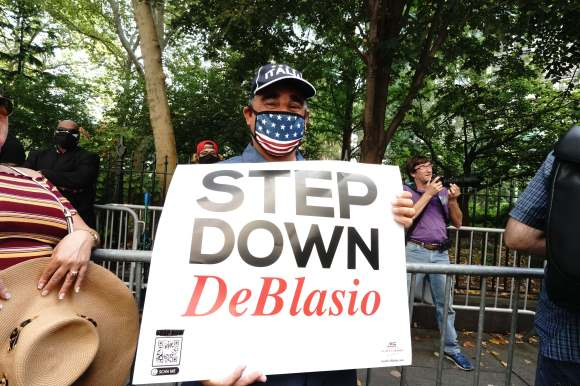 A protester is pictured holding a sign saying: 'STEP DOWN DeBlasio'