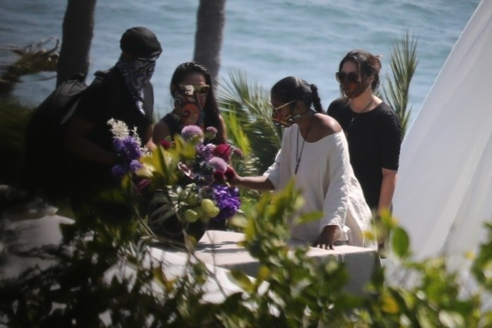 Taylor Simone Ledward se acerca a la hermosa exhibición de la mesa con la foto y las flores de Boseman