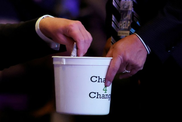 Trump put the wad of cash into a collection plate labelled 'change 4 change'