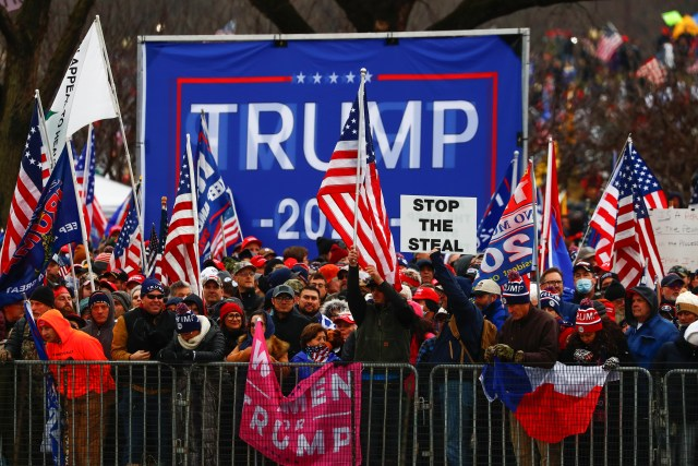 Demonstrators wave Trump and American flags and hold signs reading things like 'stop the steal'