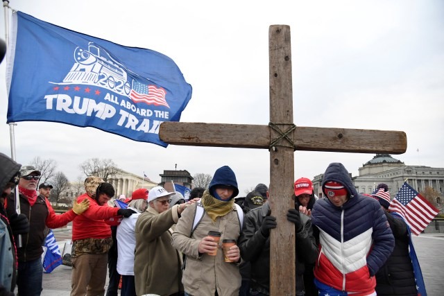 Supporters hold a cross as they gather to show support for Trump