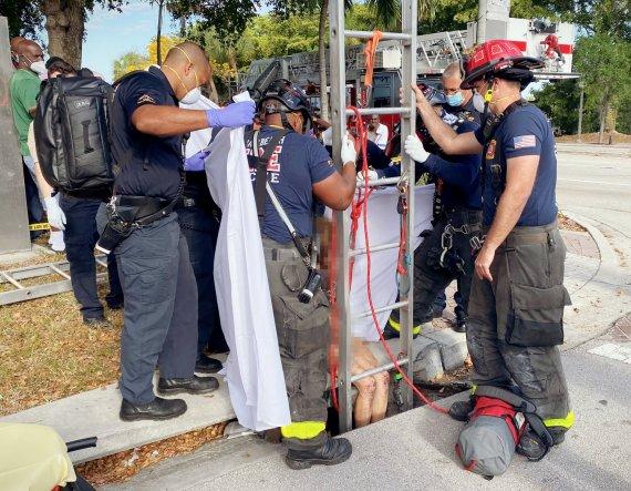 Florida firefighters hauled Lyndsey Jane Kennedy, 43, from below a sidewalk in Delray Beach yesterday