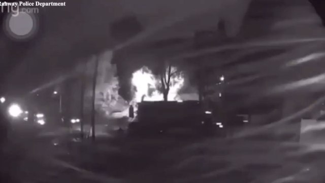 The home bursts into flames just as a large delivery truck and other cars casually pass by the spectacular flames