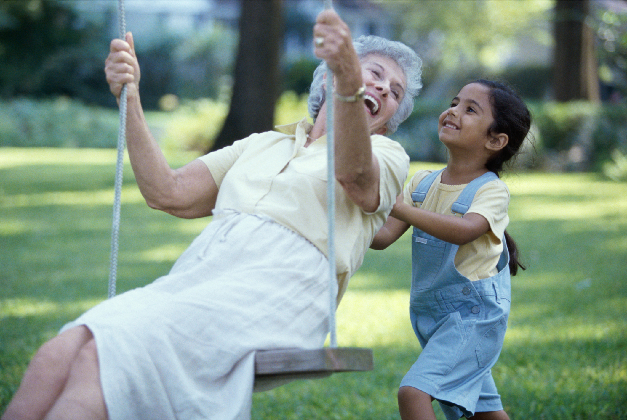 A granddaughter pushing her grandmother on a swing