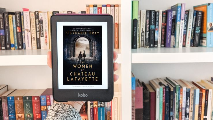 Photo of book cover The Women of Chateau Lafayette on an e-reader in front of a bookshelf