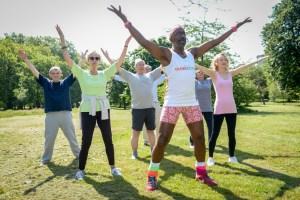 "Derrick Evans, better known as ""Mr. Motivator""  with aerobics team, Harry Nash,  Nigel Iskander, Anthony Shorter,  Hi Chu Yap, Judy Hill, Mangala Harris, Green Park, London"