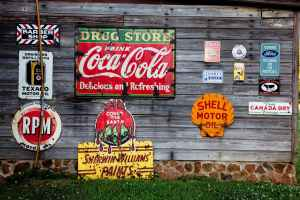 drug store drink coca cola signage on gray wooden wall with different types of advertising.