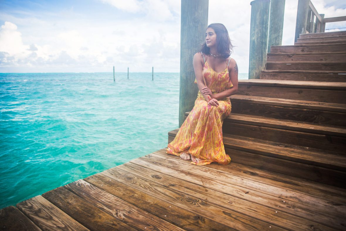A photo of me in Nassau, Bahamas on the pier looking over the turquoise ocean waters.