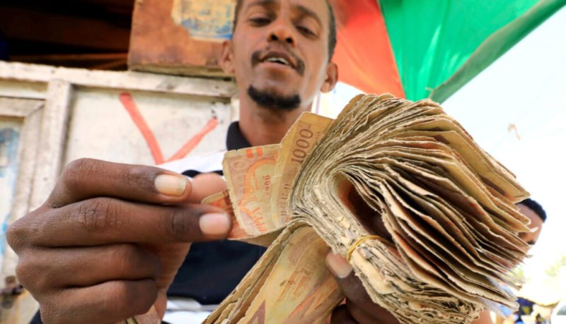 A dealer counts bundles of Somalian currency at an open air currency exchange bureau within the Hamarweyne open air market in Mogadishu
