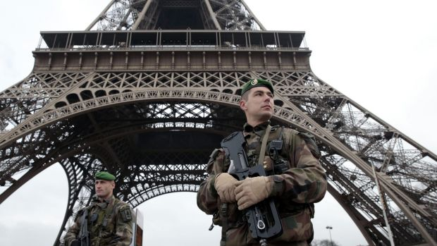 French soldiers patrol in front of the Eiffel Tower on Wednesday after terrorists killed at least 12 people in Paris.