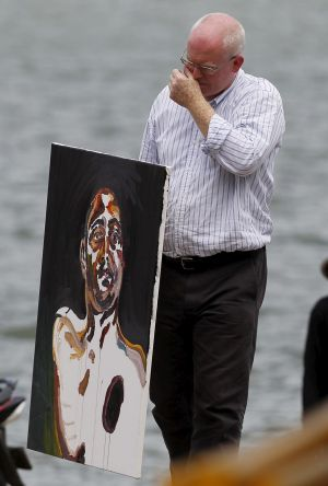 Lawyer Julian McMahon carries a self-portrait painted by Australian death row prisoner Myuran Sukumaran.