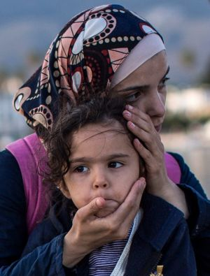A Syrian woman embraces her daughter on the Kos dockside after being escorted into the harbour by the Greek coastguard.