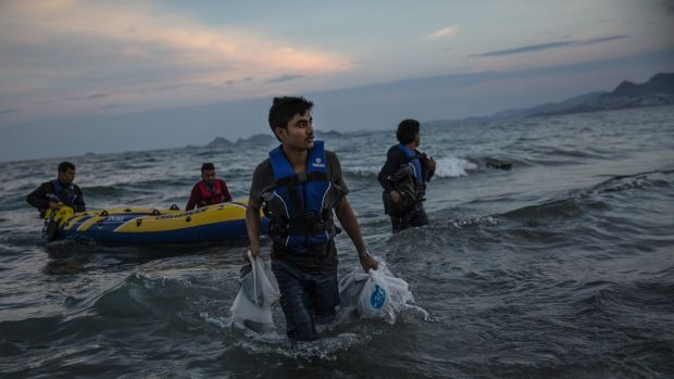 Pakistani migrants arrive on the beach in Kos, Greece, at dawn after making their way from Turkey