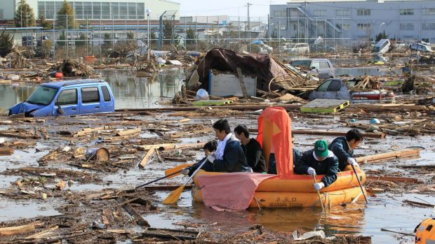 Students use a rubber raft to get food from their dormitory that submerged following the catastrophic earthquake and tsunami.
