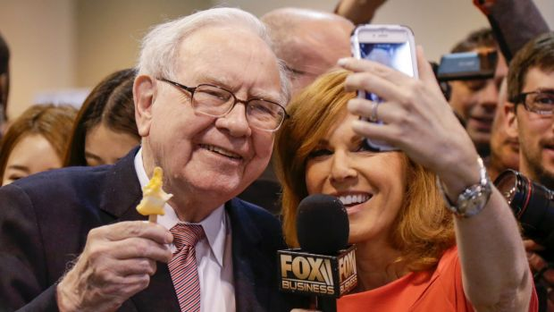 Berkshire Hathaway Chairman and CEO Warren Buffett, holds an ice cream as he poses for a selfie with Liz Claman of the ...