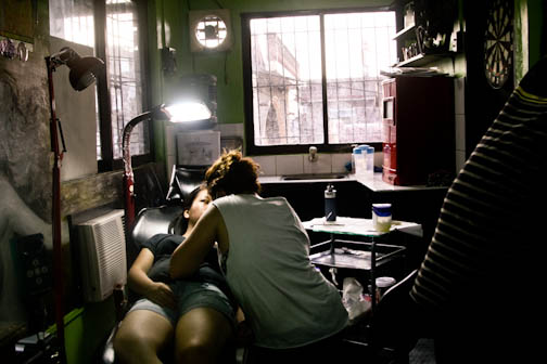 A tattooing session is being performed by Marni Cruz in a cramped tattoo studio in Losa Banos, Laguna. photo by: Chris Quintana