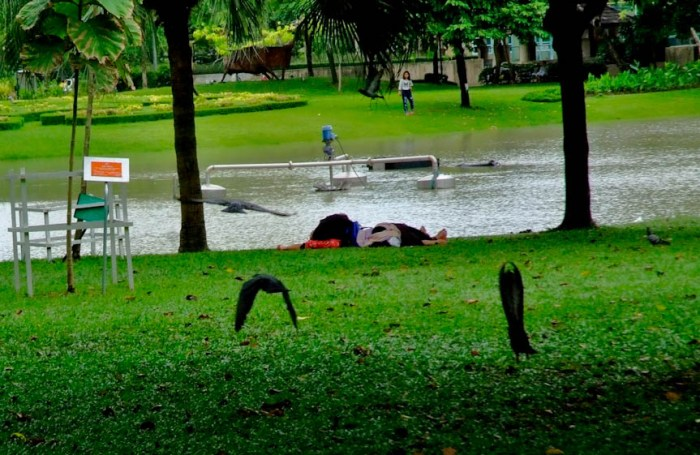 People sleeping on the grass Bangkok, Thailand. Photo by: Sonny Yabao