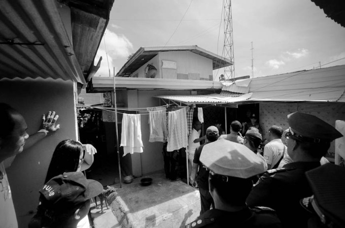 A drug suspect tries to evade authorities by climbing up their house's roof, fearing apprehension. He was later assured that authorities were only there to talk to him as part of Oplan TokHang. Photo by: Dax Simbol.