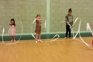 The Everyman Class practicing with long ribbons for a dance routine.
