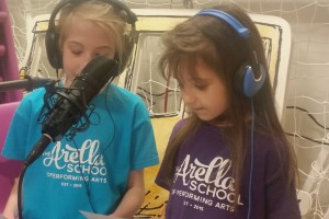 Students from our Everyman Class recording their singing with a microphone.