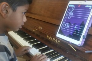 A piano student practicing their note reading skills with an app called Note Rush.