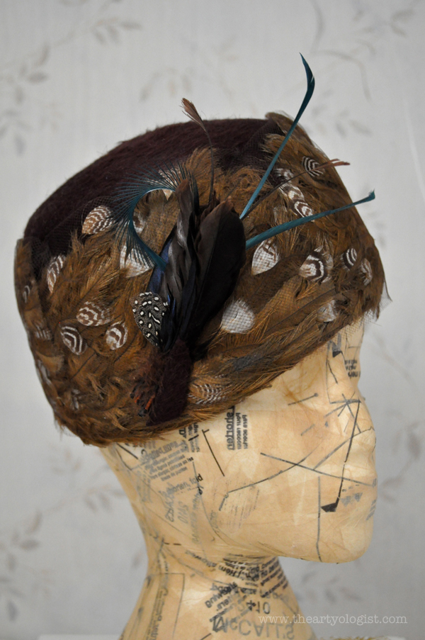 the artyologist image of vintage 1960's feathered hat after in front of wallpaper