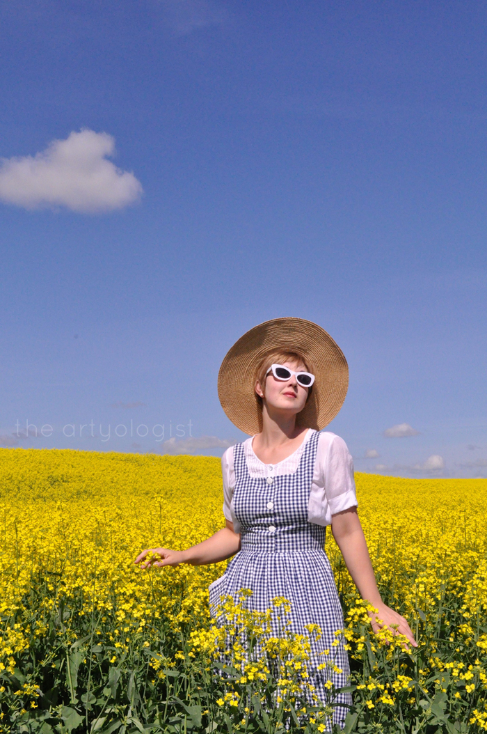 sunglasses and pinafore in the canola field the artyologist