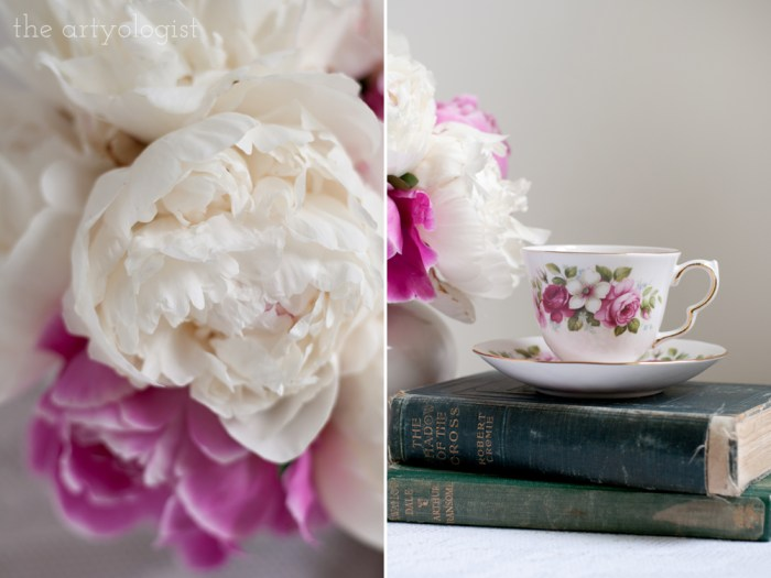 a closeup of a peony bouquet and a teacup on top of books