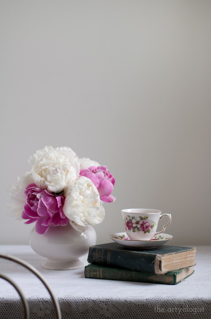 a table set for tea with a bouquet and floral teacup