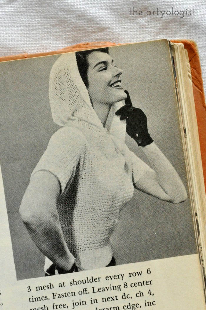 lady wearing a vintage short sleeved hooded sweater with the hood up